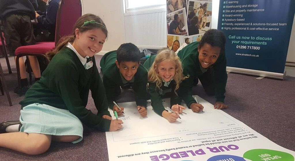 4 smiling primary pupils signing an EqualiTeach pledge, promising to tackle bullying in their school.
