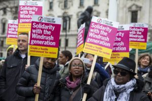 Image of people holding placards that read 'Solidarity with the Windrush generation'