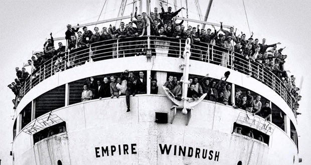 Photo of the Empire Windrush ship with many people waving from it